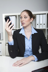 Frau geschockt von Nachricht SMS im Büro