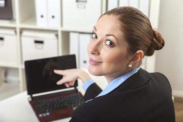 Frau zeigt auf den Laptop Bildschirm