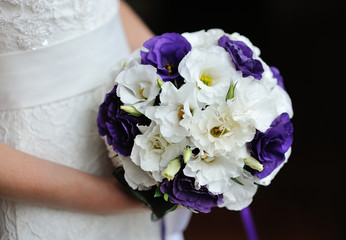 Bride holding wedding bouquet of purple flowers