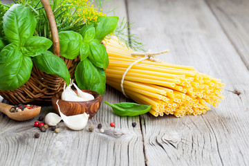 Fresh pasta and italian ingredients on wooden table