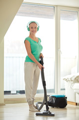 happy woman in headphones with vacuum cleaner