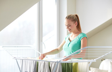 happy woman hanging clothes on dryer at home