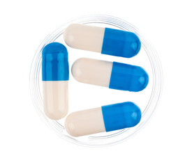 Close up of blue medical capsules on white background