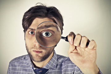 Man searching through a magnifying glass to the newspaper