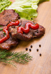 tasty grill meat with sauce and green on wooden background