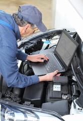 Automechaniker mit Laptop bei Analyse