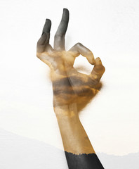 Double exposure of OK gesture and sunset