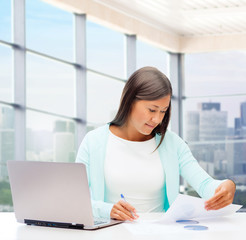 smiling woman with laptop computer and papers