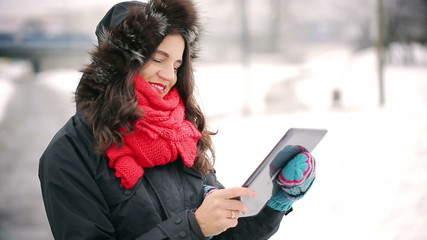 Woman using tablet and smiling to the camera in park at winter