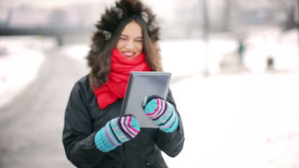 Woman walking in the park at winter and chatting on tablet