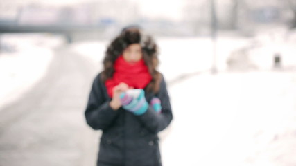 Woman walking in the park at winter and texting on smartphone