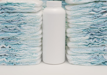 Two stacks of disposable baby diapers and a talc powder bottle