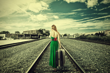 Woman with suitcase walking away on rail tracks talking on phone
