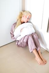Blonde Frau sitzend im Flur