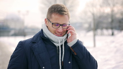 Man talking on cellphone and smiling to the camera in the park