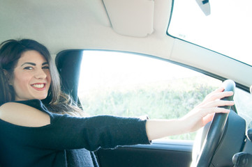 beautiful girl driver inside a car in a sunny day