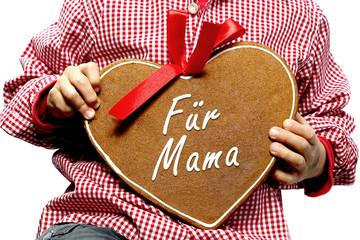 Kind hält Herz mit Aufschrift Für Mama