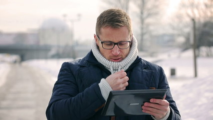 Man using tablet in the park at winter time and warming up hands