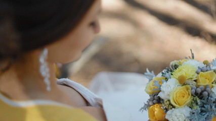 Young woman hold yellow bouquet in her arms