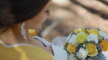 Bride look at her wedding bouquet