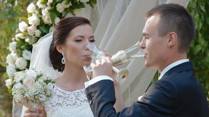 Bride and groom drink champaign