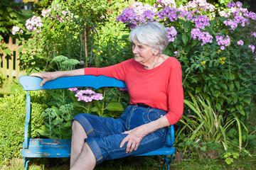 Senior Woman Relaxing at the Garden Bench.