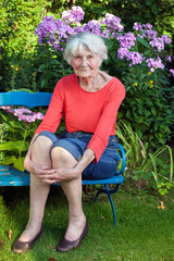 Smiling Old Woman Sitting on the Garden Bench.