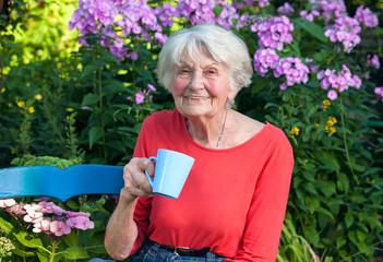 Happy Grandma Having a Coffee at the Garden.