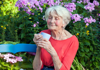 Thoughtful Old Woman with Coffee at the Garden.