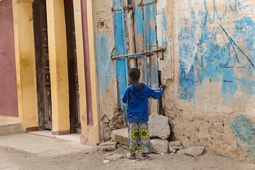 Niño de raza negra solo en la calle.