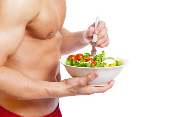 Fit man holding a bowl of fresh salad on white background