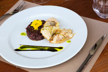 Codfish with black rice and sauce