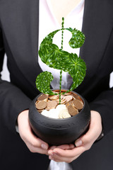 Dollar sign growing in ceramic pot full of coins, pot in hands