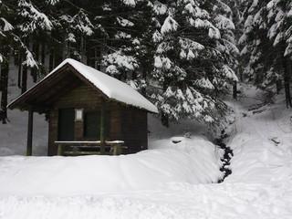 Holzhaus im Schnee neben Bach