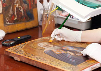 restorer works on old gilded icon with brush