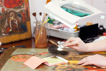 Restorer working on the ancient icon with gold leaf