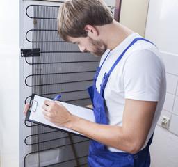 Handyman standing at the fridge