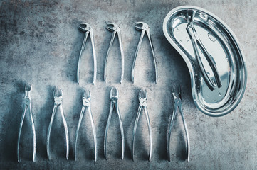 Forceps dental pliers arranged on table with sterile dish