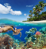 Young woman snorkeling over coral reef in tropical sea.