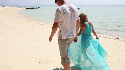 blonde girl in blue and guy go away along beach photographer