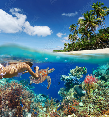 Young woman snorkeling over coral reef in tropical sea. - 78135376