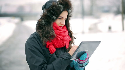 Happy woman standing in the park at winter time and using tablet