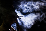 Dark of a young man smoking over a black background