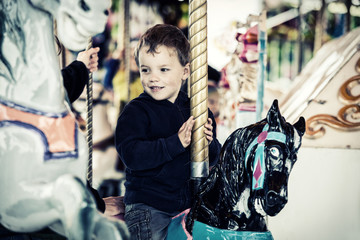 Happy Boy on a Carousel Horse Ride - Retro Filtered