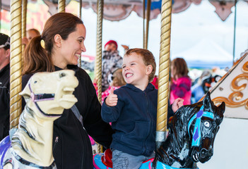 Boy and Mother on Carousel Smiling at Each Other