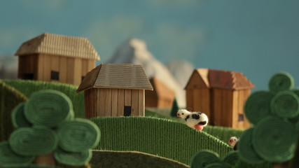 Alpine landscape with village, cows and farms made of wool