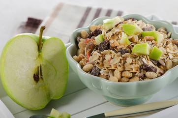 Muesli and green apple for healthy breakfast.
