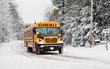 canvas print picture - School Bus Driving in Winter on a Snow Covered Road