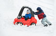 canvas print picture - Young Boy Gives a Push to his Brother's Car Stuck in the Snow