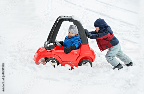 Young Boy Gives a Push to his Brother's Car Stuck in the Snow